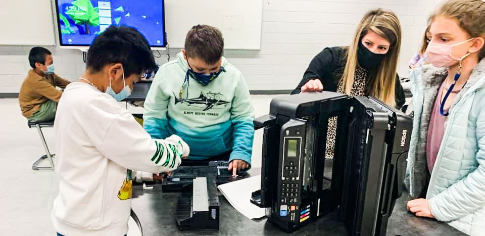 group of three students and teacher working on an old printer