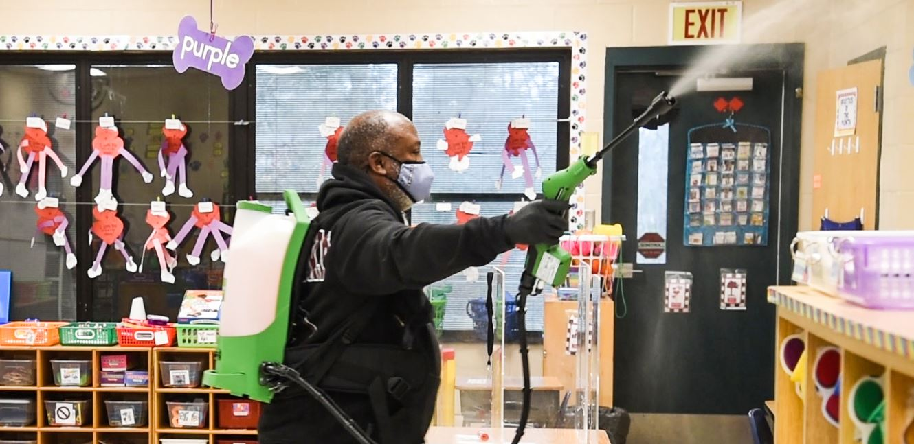 robert holmes spraying a room with an electrostatic sprayer