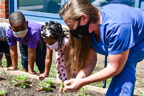 heather tamayo with students in the garden