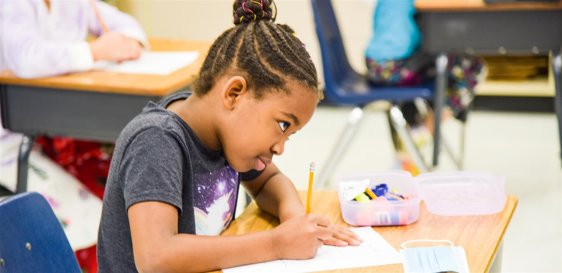 first-grade student writing at desk in class
