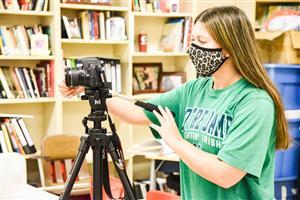 SHS student wearing a college t-shirt and mask while operating a camera