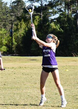 girl catching ball with stick during practice