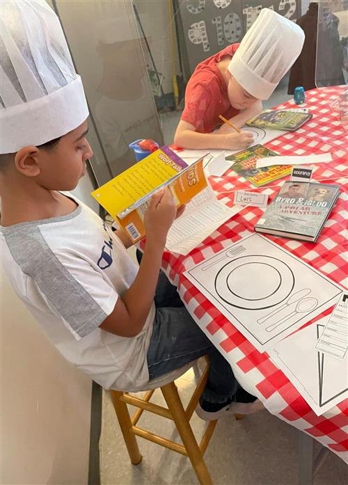 two boys in chefs hat participating in book tasting activity