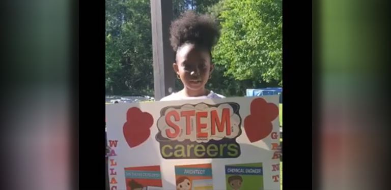 Student holding sign about STEM education