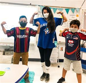 three students participate in showing off their favorite jerseys at GCE