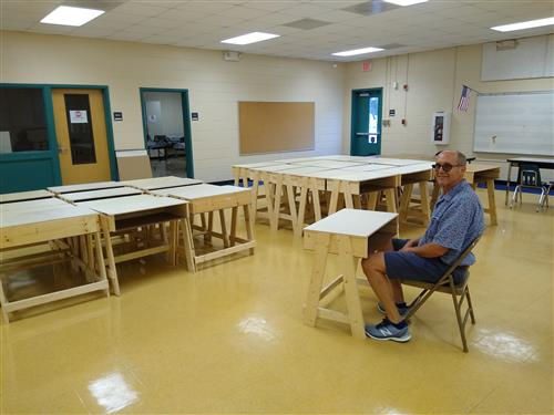 Rotary Member sitting one of the constructed desks