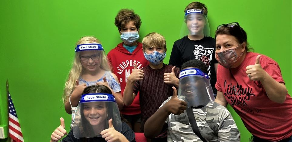 WMNE Marrington News Team members and teacher giving the thumbs up in front of a green screen