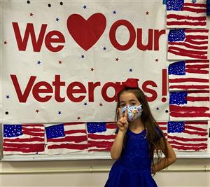 "student in front of a board that read ""we [heart] our veterans!"" at MRE"