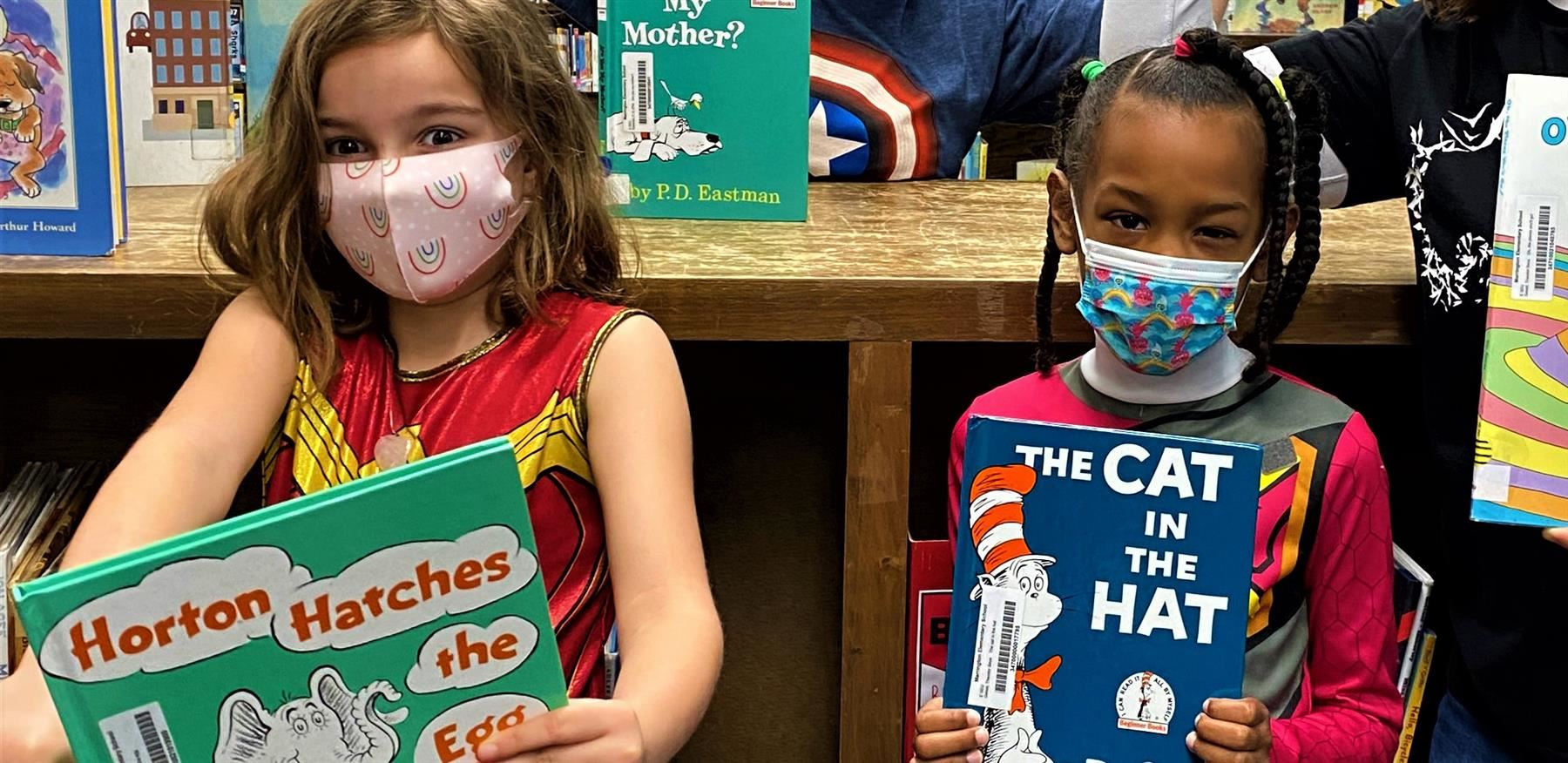 two girls at MNE holding up Dr. Seuss books