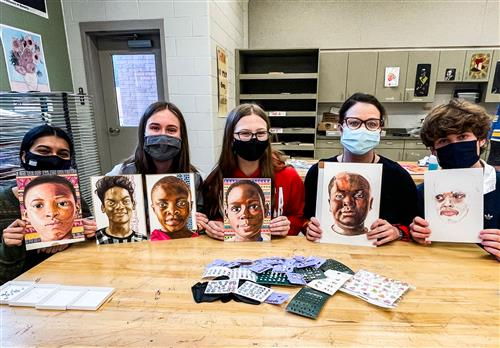 four students (and art teacher paige duvall) hold up ongoing portraits