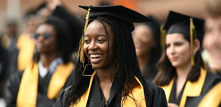 Photo of smiling graduate in crowd