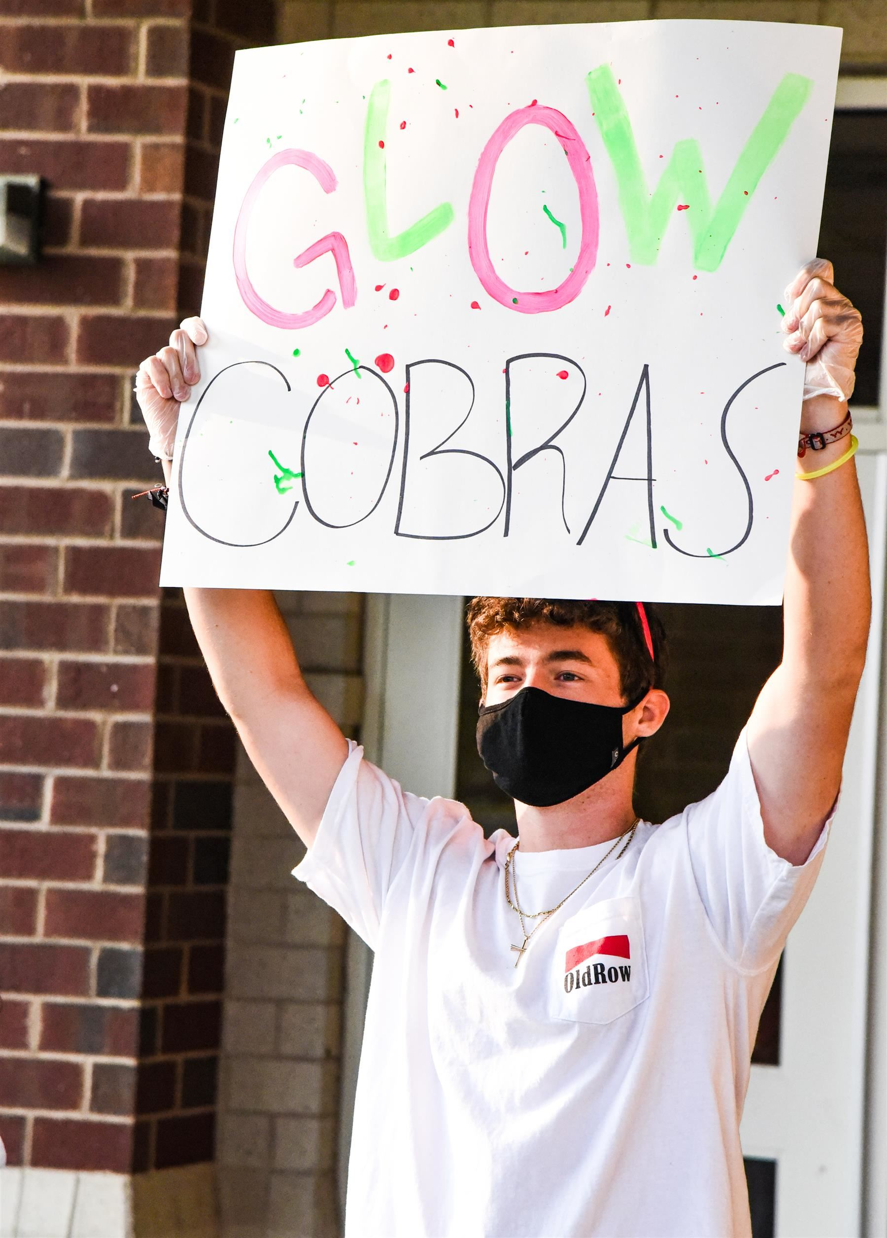 "student holds up a sign that reads ""Glow Cobras"""