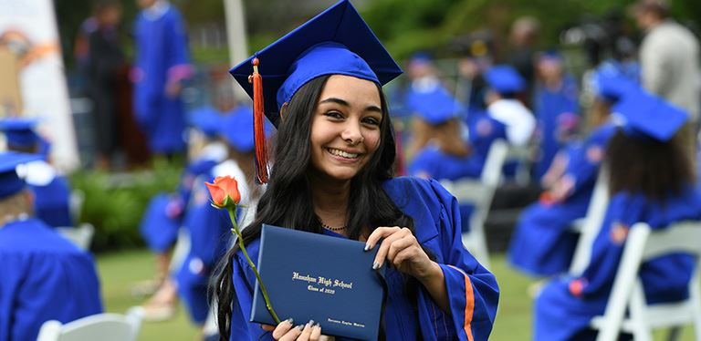 Photo of female HHS graduate with diploma and orange rose