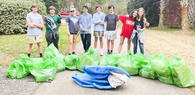 group photo of high school students with collected bags of trash and kiddy pool
