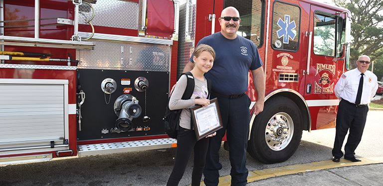 Photo of Rylee with the fire chief