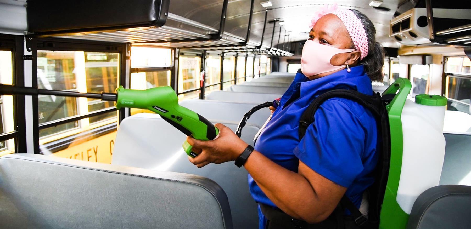Bus driver Ruthie Haskell sprays down the inside of a bus