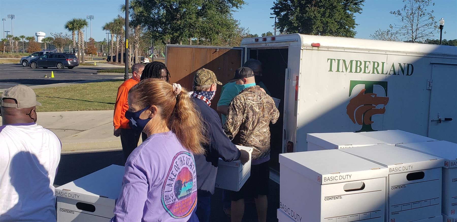 volunteers assemble meal boxes at Timberland High
