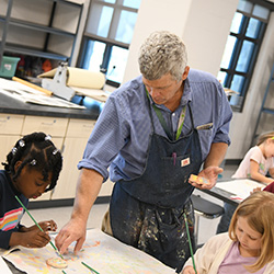 Art teacher gives students painting instructions